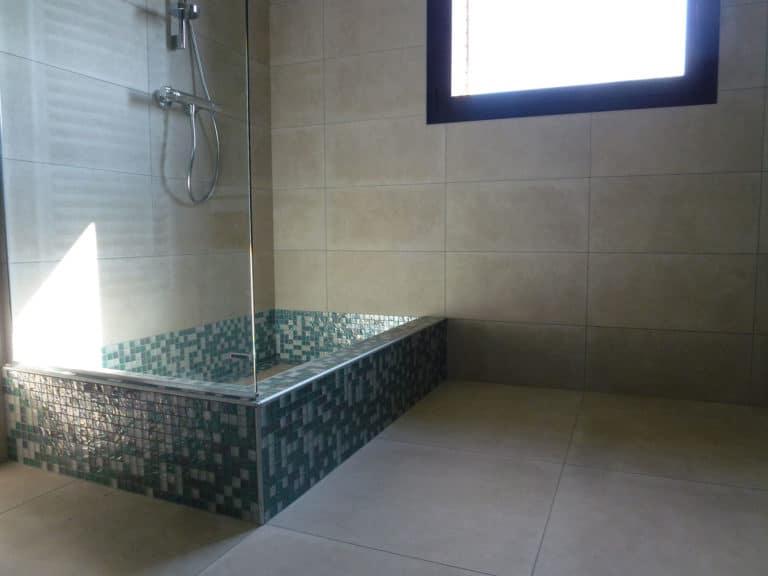 Douche avec bac d'une hauteur de 20 cm construit avec des mosaïques