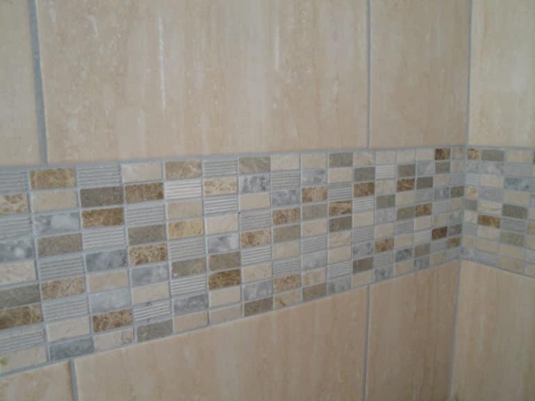 Mur d'une salle de bain avec une rangée horizontale de mosaïques