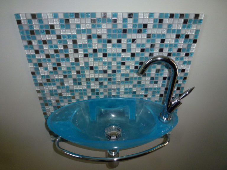 Lavabo bleu translucide sur un mur en mosaïque bleu-noire-blanc