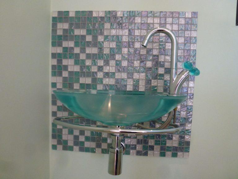 Lavabo vert sur mur à mosaïque vert-gris-blanc