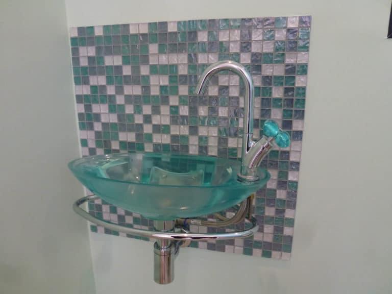 Lavabo vert translucide devant un mur à mosaïques de même couleur