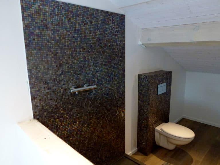 Des toilettes suspendues à une tête de cloison -chasse d'eau faites de mosaïque